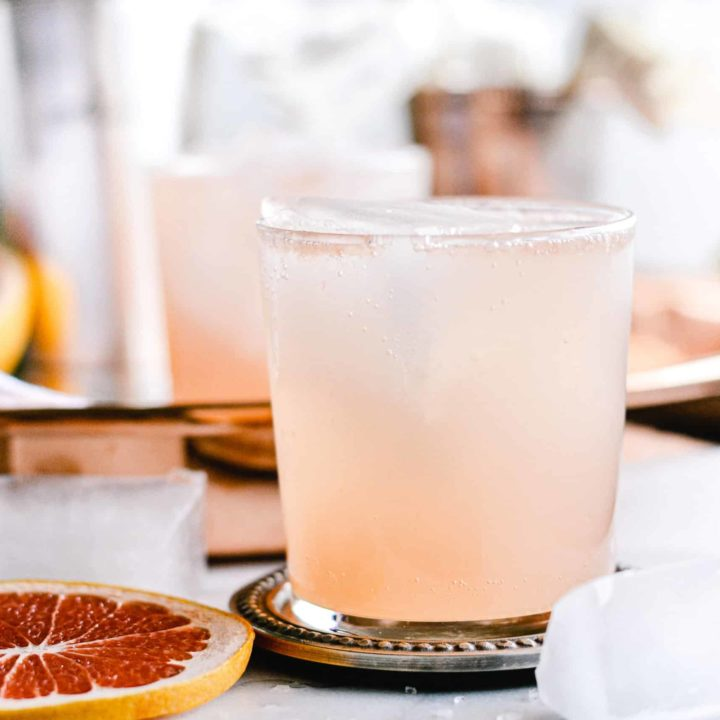 Grapefruit Collins Cocktail with Rosemary Simple Syrup on silver coaster.