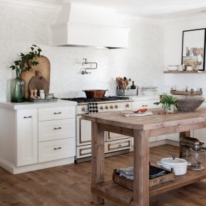 Farmhouse kitchen with white shaker cabinets and wood island.