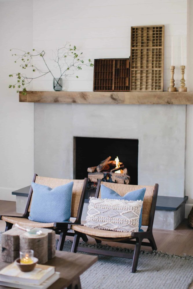 Cement fireplace with fire burning and reclaimed wood mantel with modern living room furniture