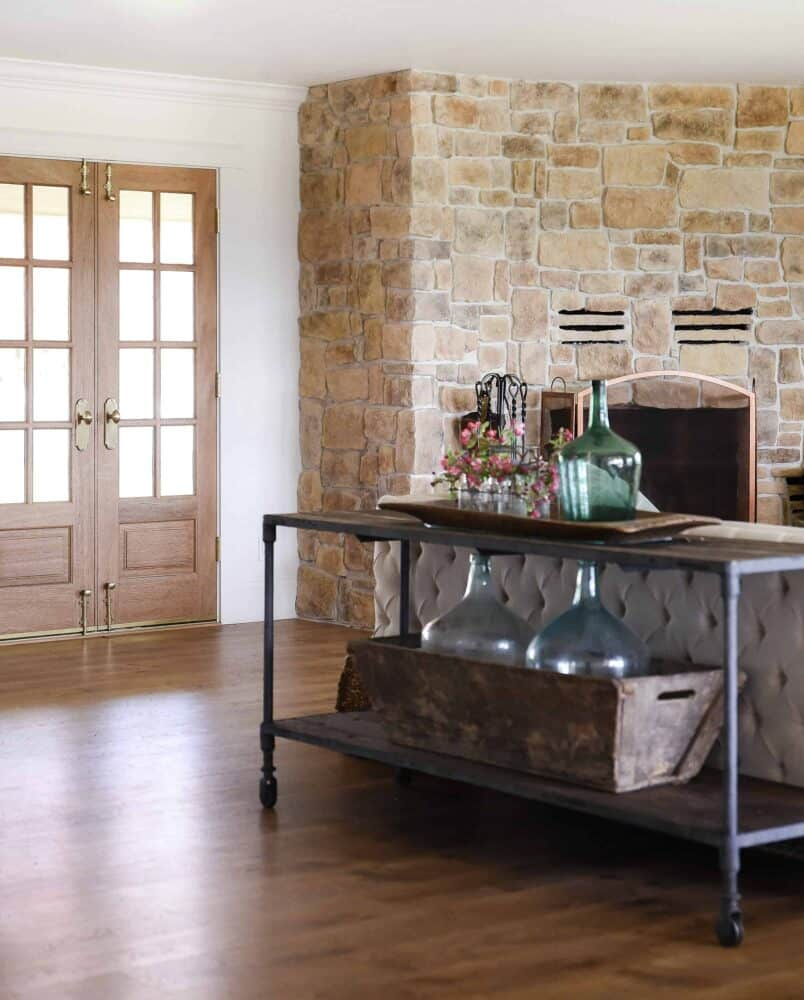 Living Room Decor with Vintage Demijohns and Wood French Doors with Stone Fireplace in Background