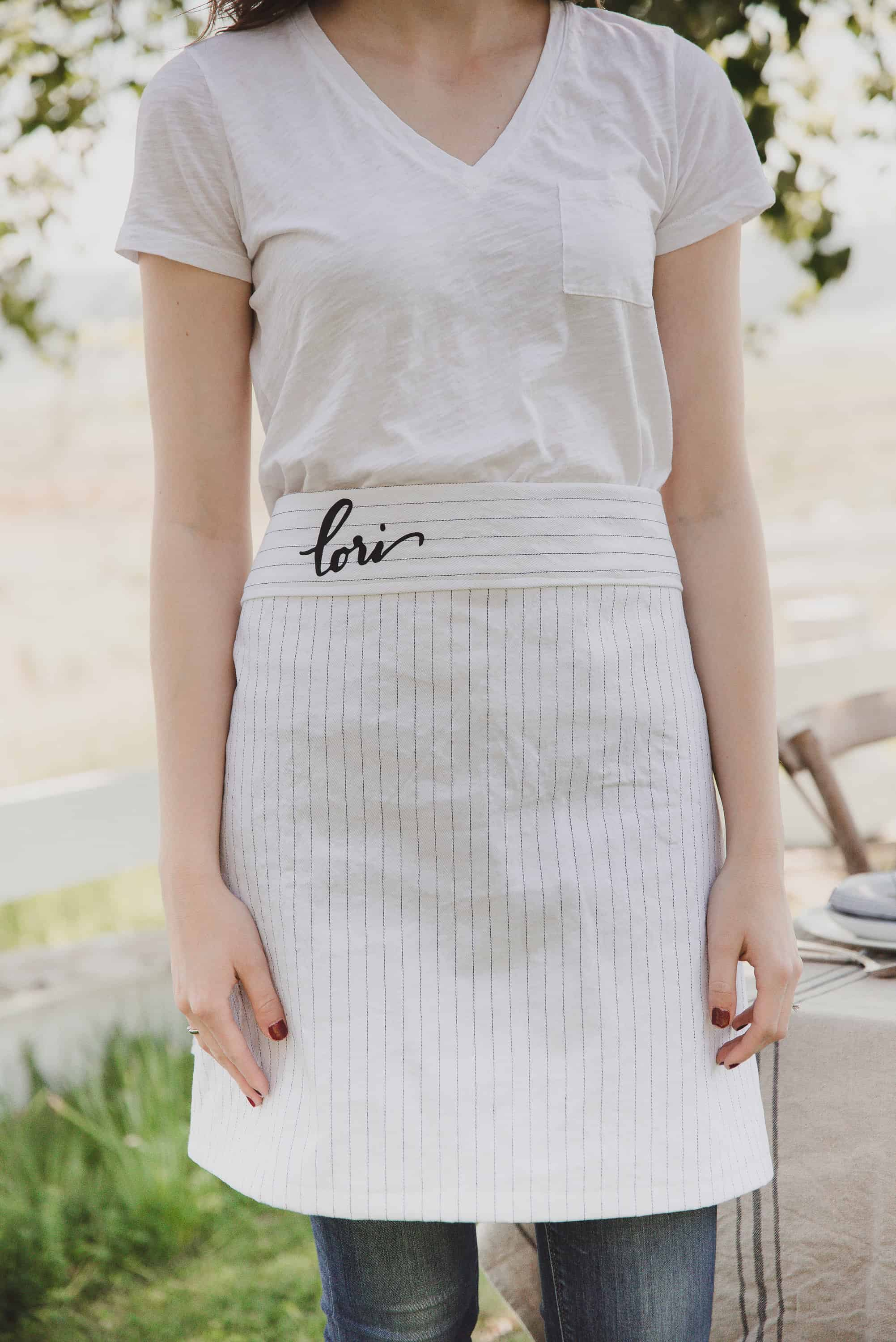 Learn how to make an easy half apron with this free apron pattern and tutorial using Brother! The personalization with HTV is the cherry on top of this darling project!