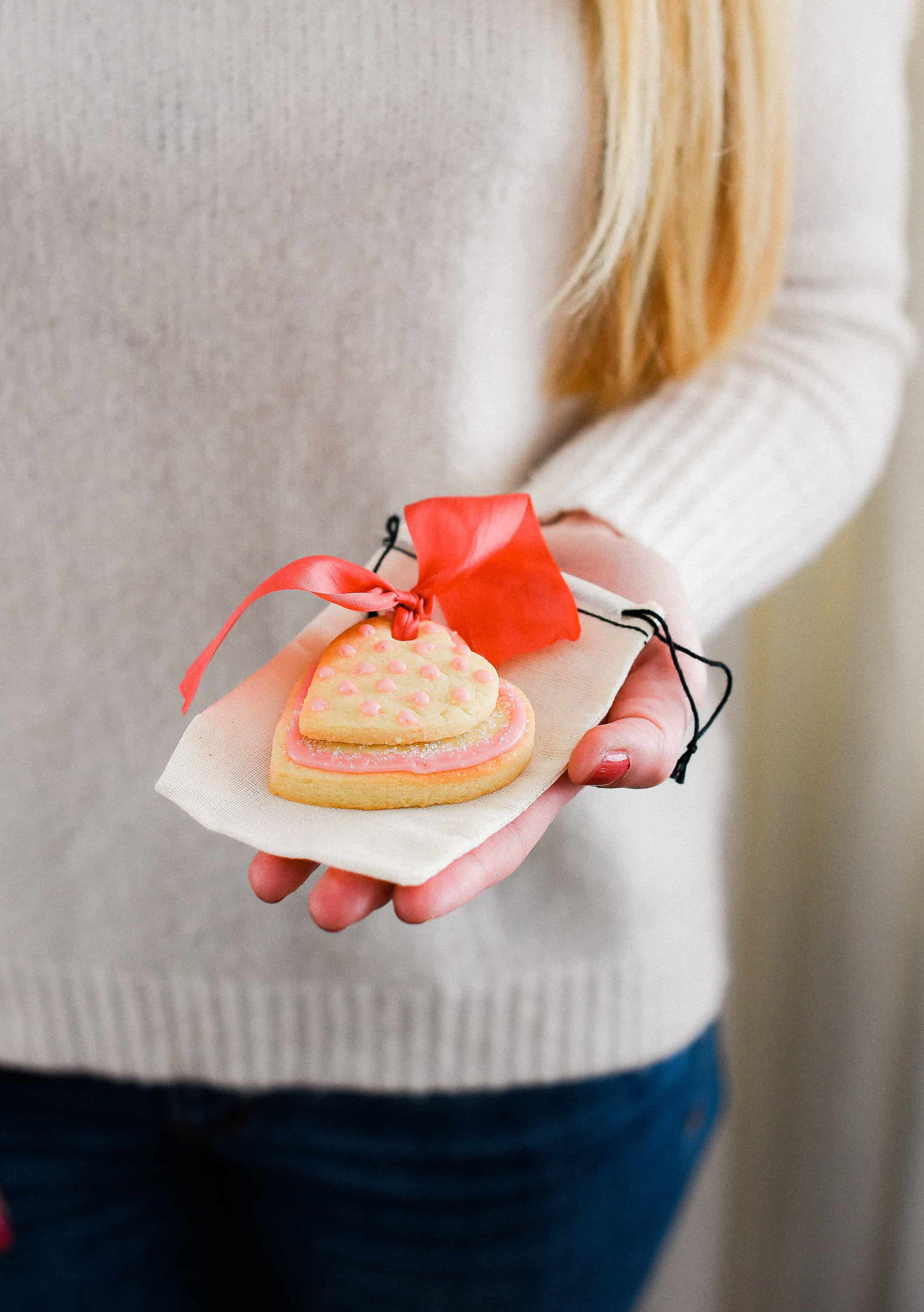 These Valentine's Day sugar cookies are topped with simple royal icing and sprinkles and couldn't be cuter! Use a little ribbon to turn these Valentine's Day sugar cookies into the sweetest Valentine treat!