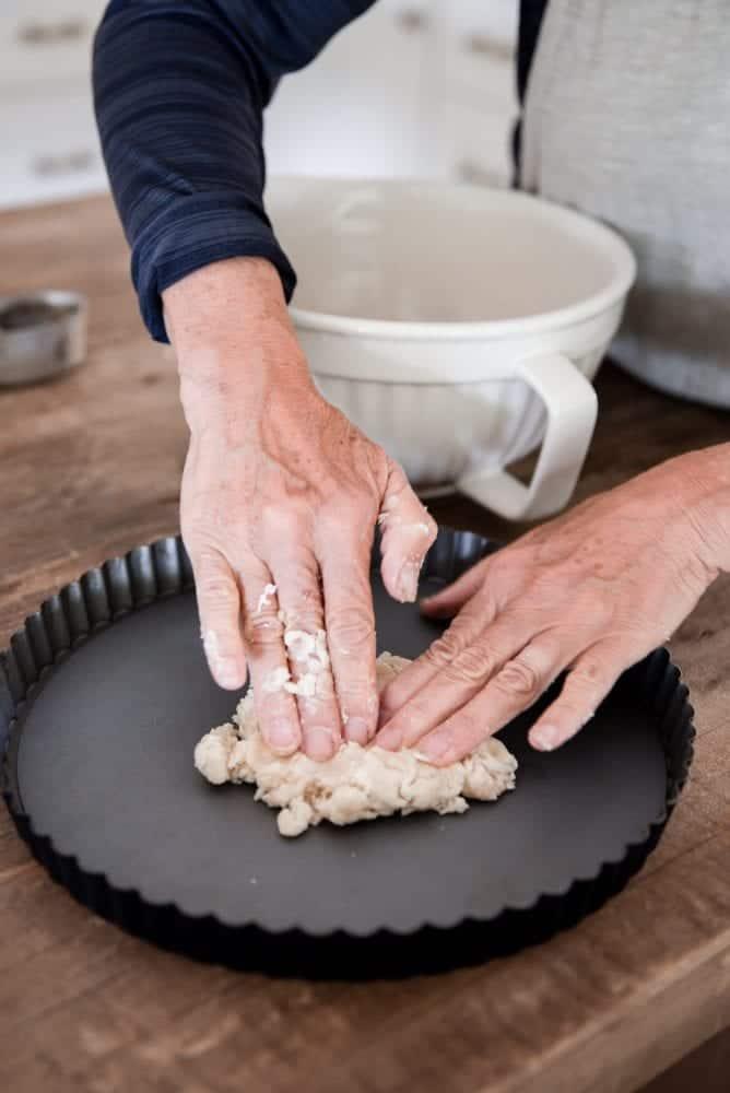 Woman pressing dough into tart pan