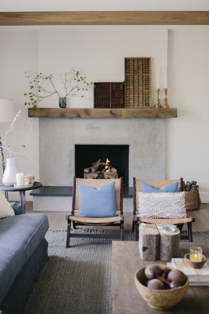 Cement fireplace with rustic wood mantel