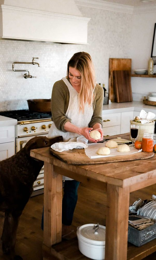 Pizza dough being made in a bright kitchen on wood table