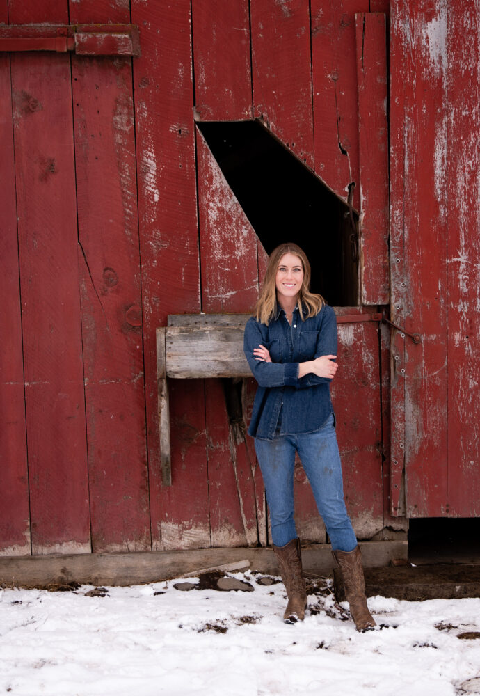 Girl standing in front of red barn in denim and boots