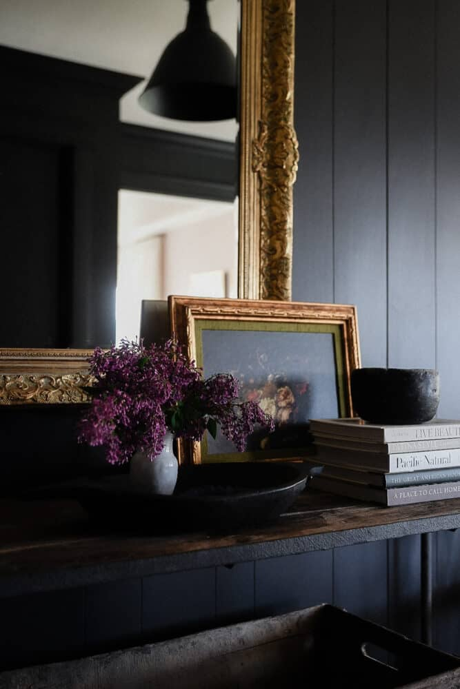Dark entryway with mirror and oil painting on wood table