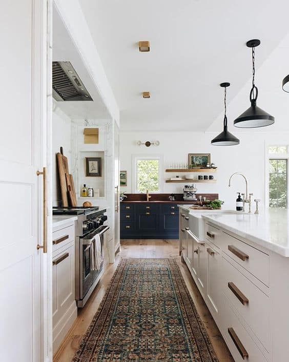 Large white kitchen with black and brass accents