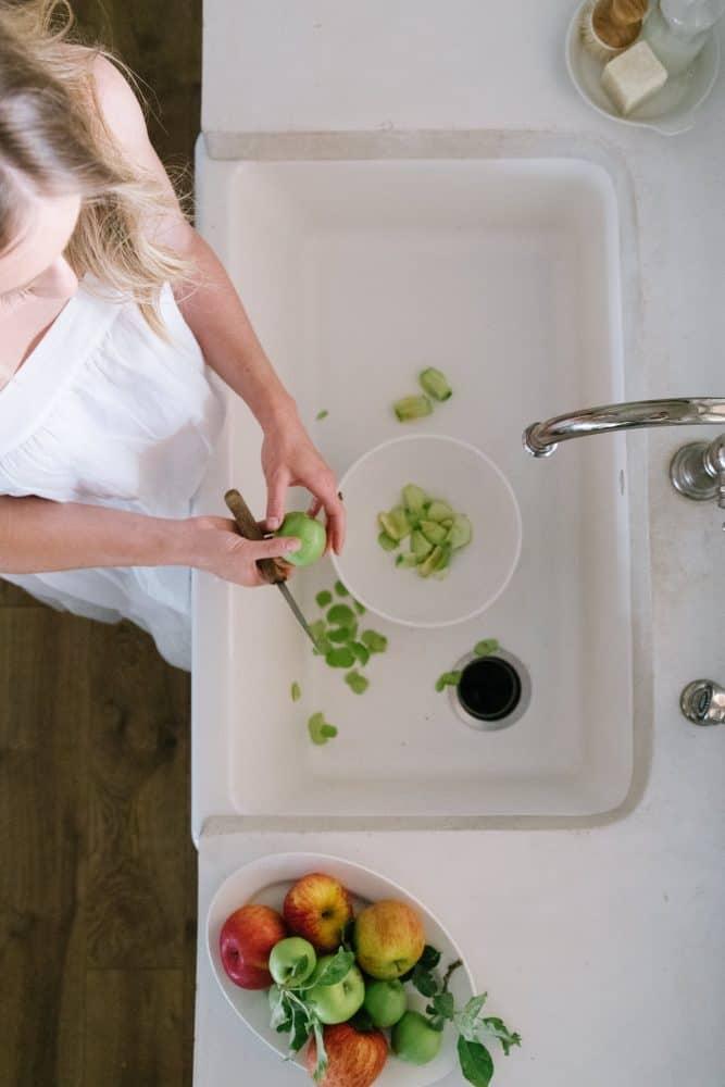 Girl peeling apples in farm sink