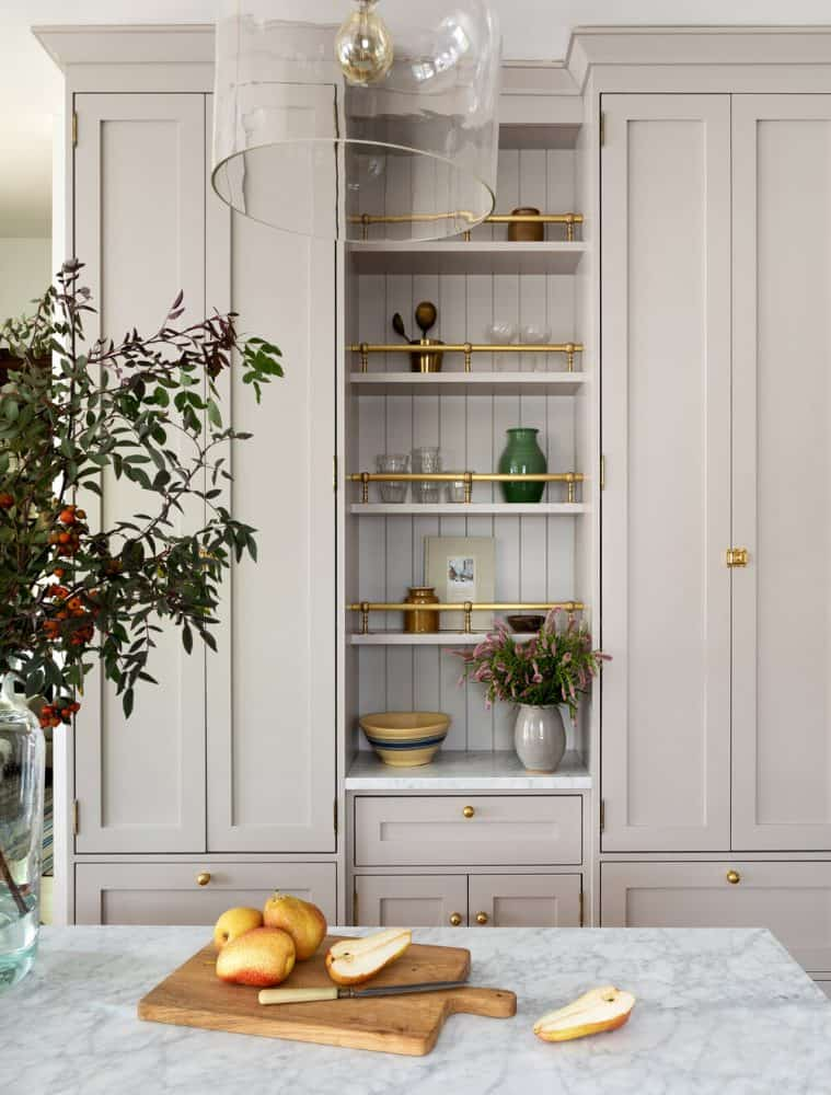 Creme colored cabinets with open shelving and brass rod detail