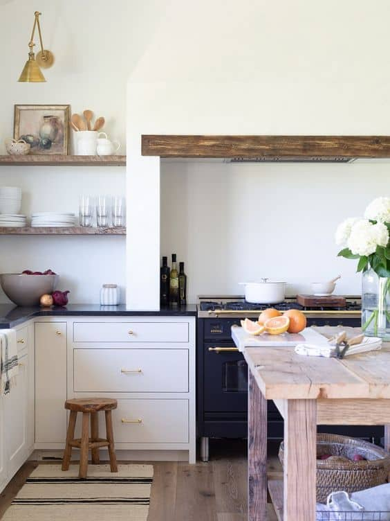Wood floating shelves in a white kitchen with art and housewares