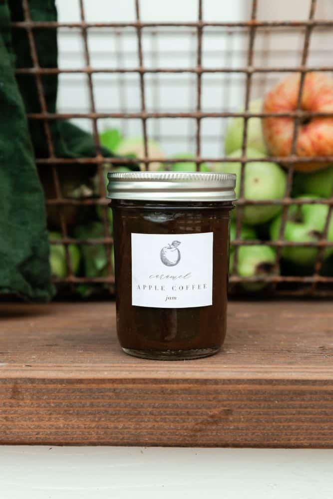 Apple preserves in mason jar in front of basket of apples
