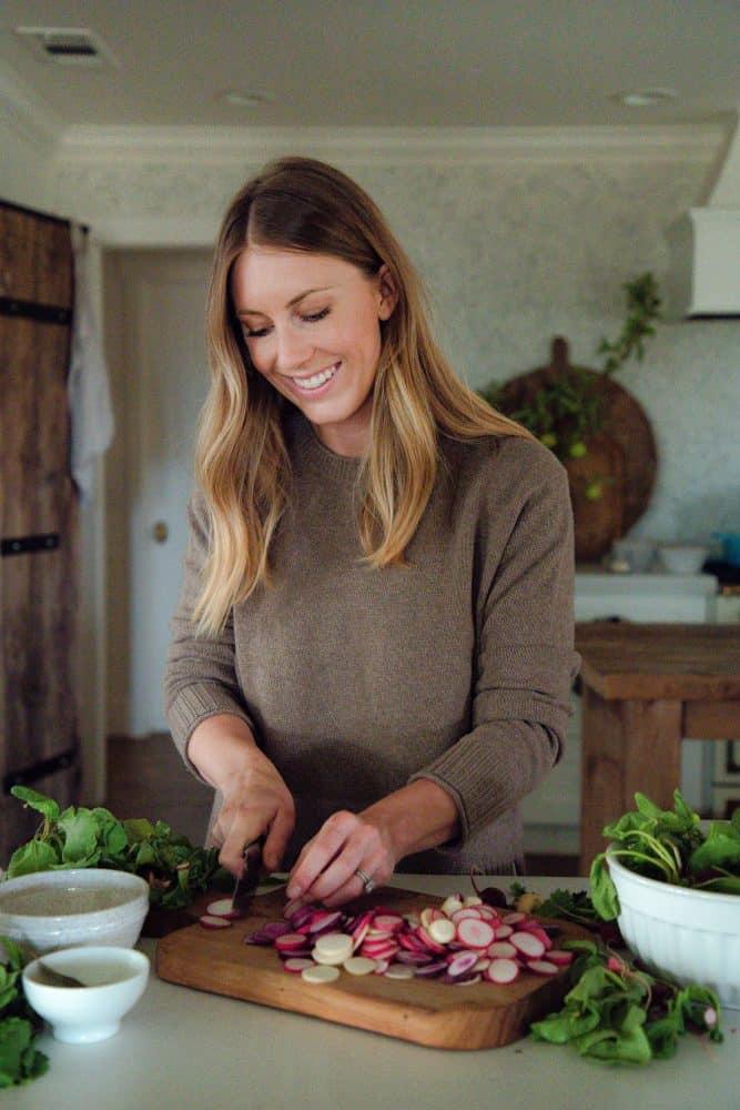 Girl cutting radishes in farmhouse kitchen