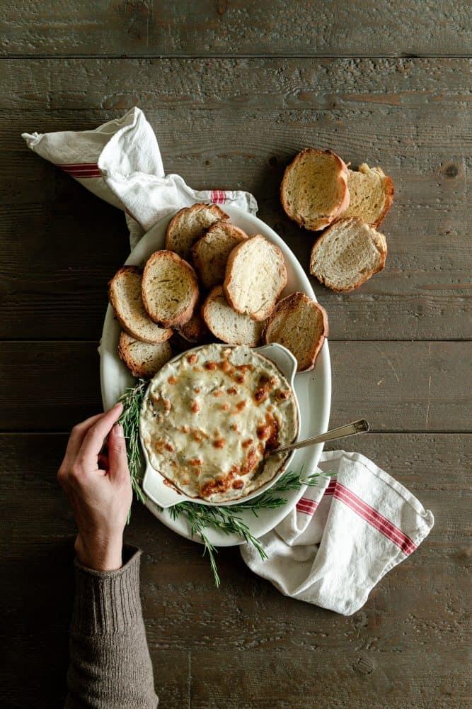 platter of cheesy artichoke dip with bread