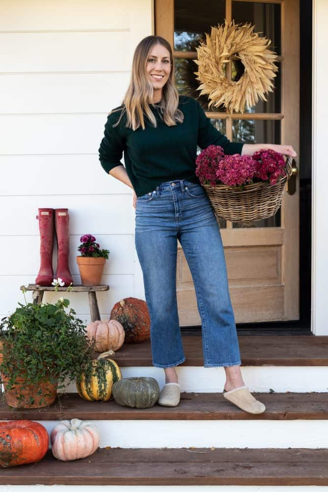 Girl holding basket of pink mums on fall porch