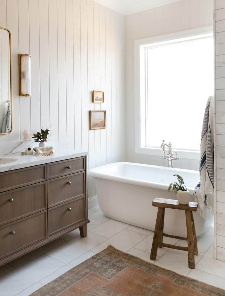 Grey bathroom with marble tile and oak vanity with free standing tub and vintage rug