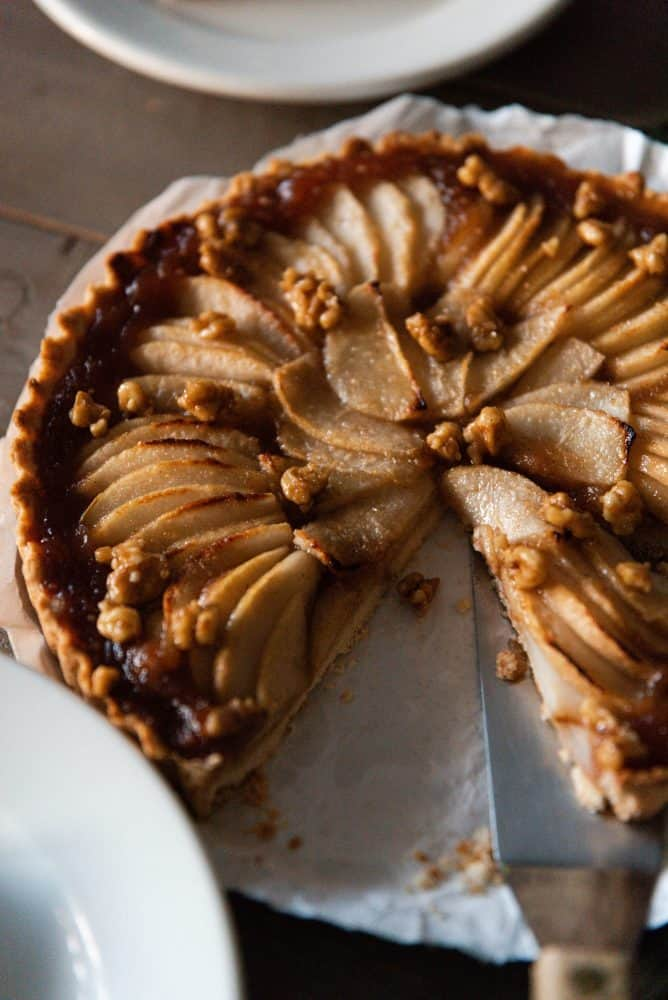 Pear tart with candied walnuts on table.