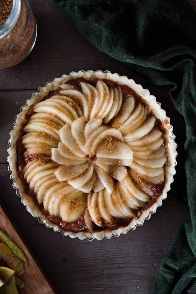 Prepared pear tart in tart dish ready to go in oven.