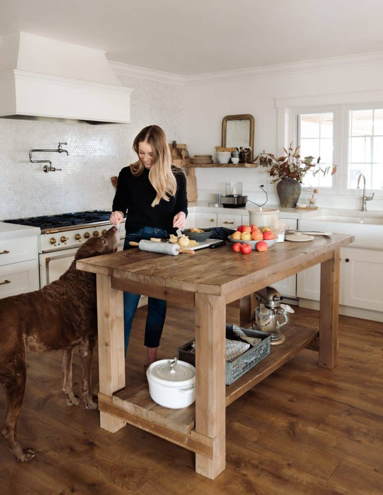 Girl at wood island in farmhouse kitchen giving brown dog a treat