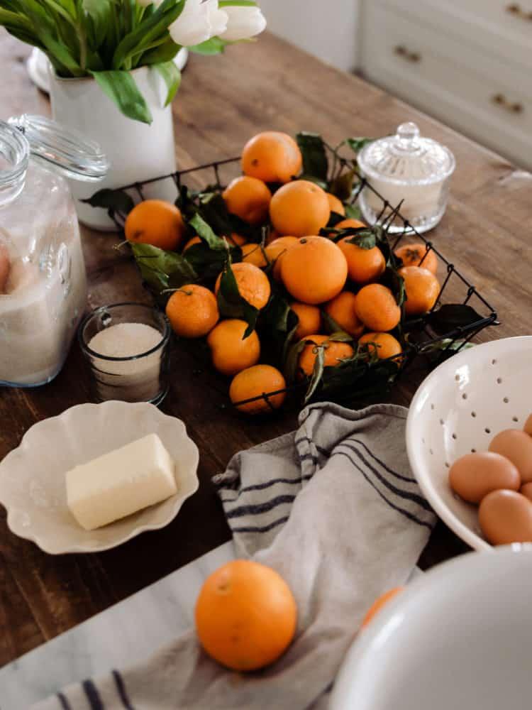Ingredients for orange curd on wood countertop: oranges, butter, eggs, sugar.