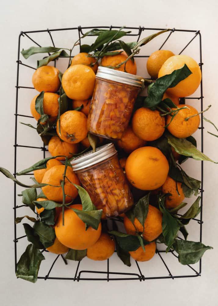 Basket of oranges with jars of orange marmalade sitting on top.