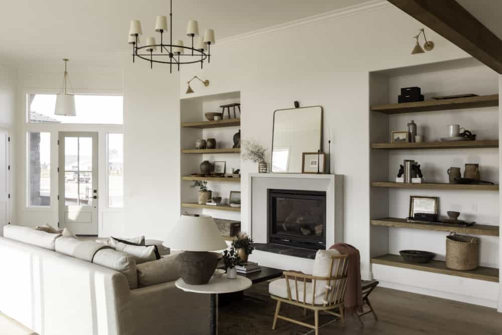 Swiss coffee living room with cement fireplace surround and floating wood open shelves with blue door.