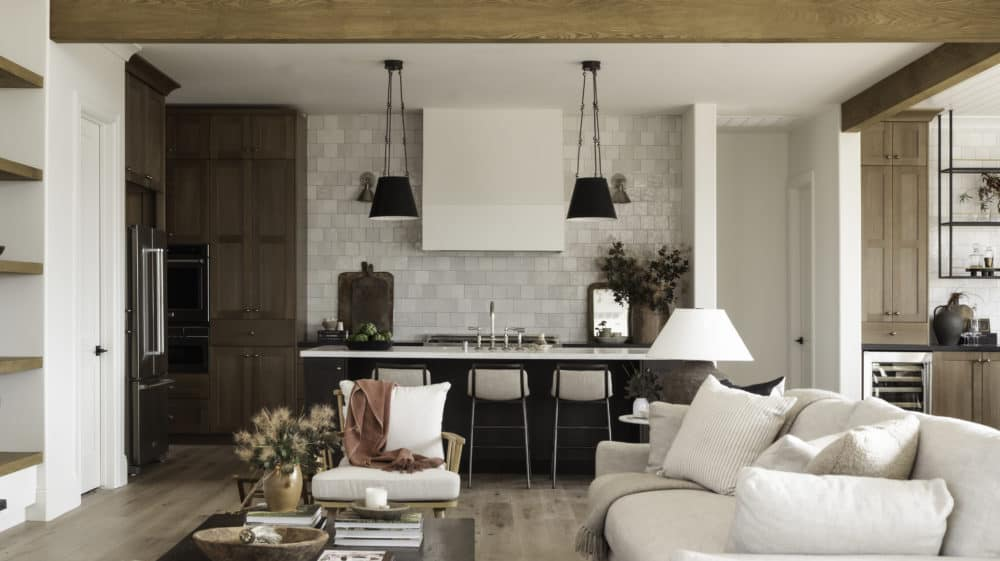 Beautiful dream kitchen design with white oak cabinets and black kitchen pendants with marble countertops and open floor plan by Boxwood Avenue Interiors