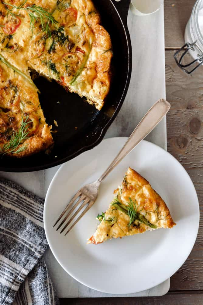 Baked frittata in a cast iron skillet on a marble board with slice on a plate with a fork.