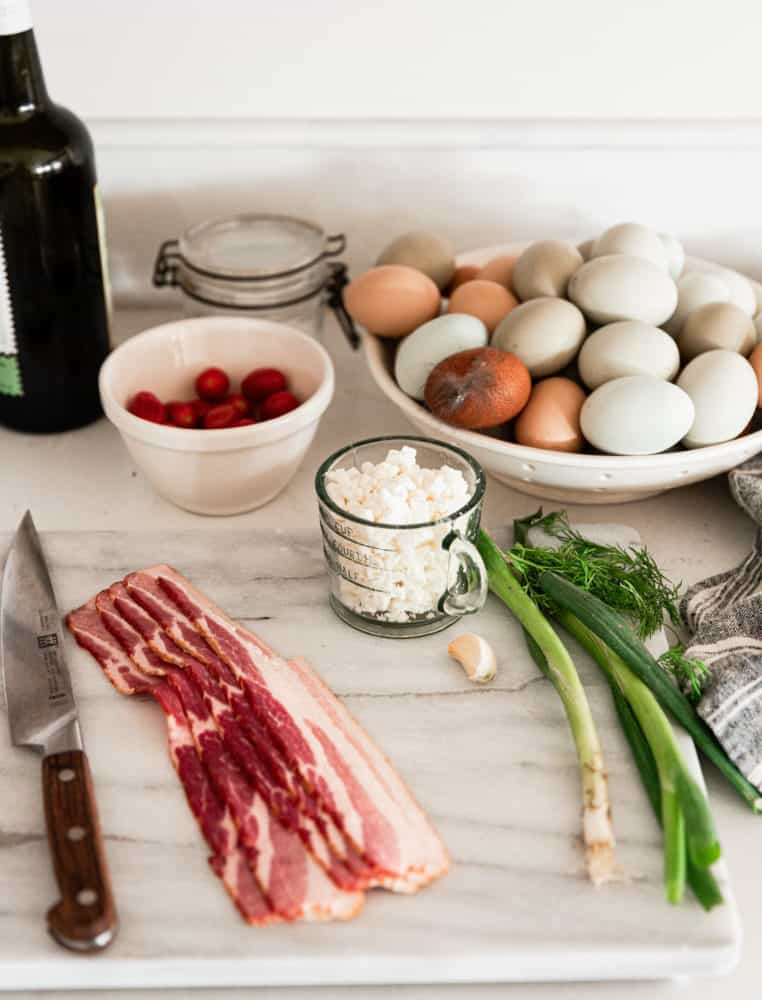 Ingredients for a frittata recipe with bacon, tomatoes, and farm fresh eggs on display on a marble cutting board.