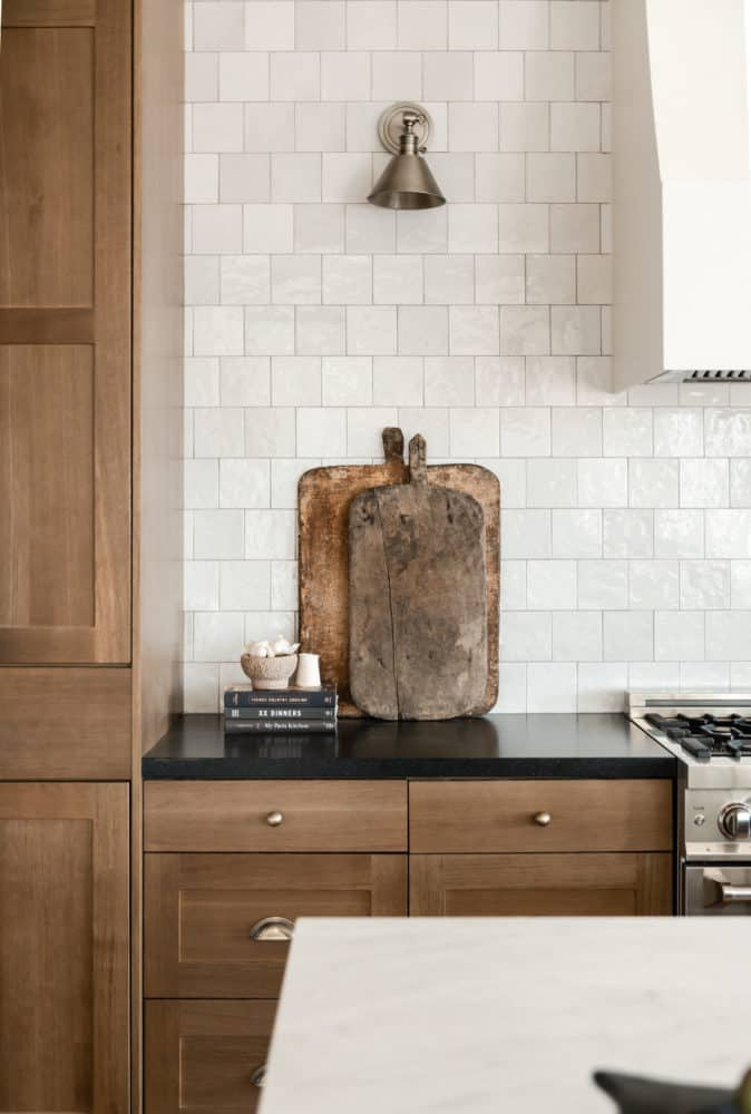 Vintage cutting boards in dream kitchen interior design by Boxwood Avenue Interiors with white oak cabinets Cloe backsplash and marble countertops.