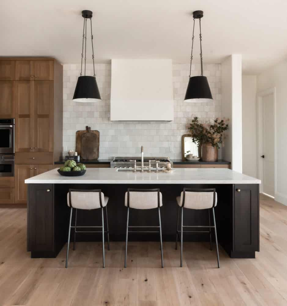 Dream kitchen interior design by Boxwood Avenue Interiors with dark island and white oak cabinets with black pendants and marble countertops.