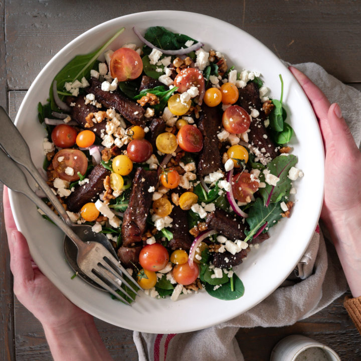 A beautiful steak salad topped with tomatoes in a large white salad bowl.