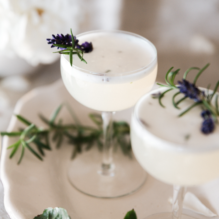 Lavender vodka fizz cocktail on a table with roses and rosemary on a table.