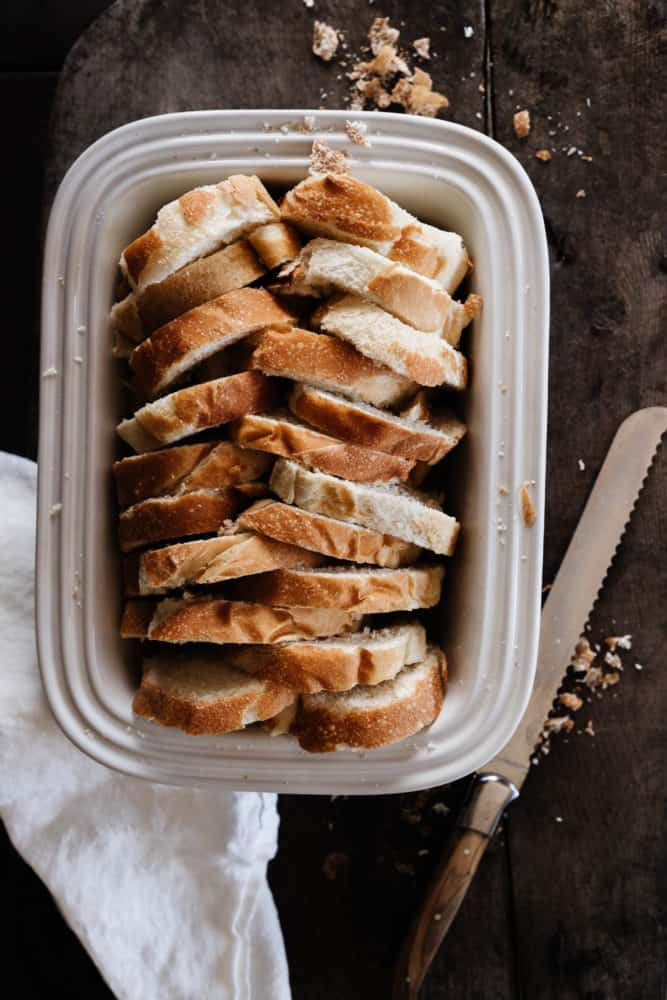 Bread arranged in a herringbone pattern in a white baking dish
