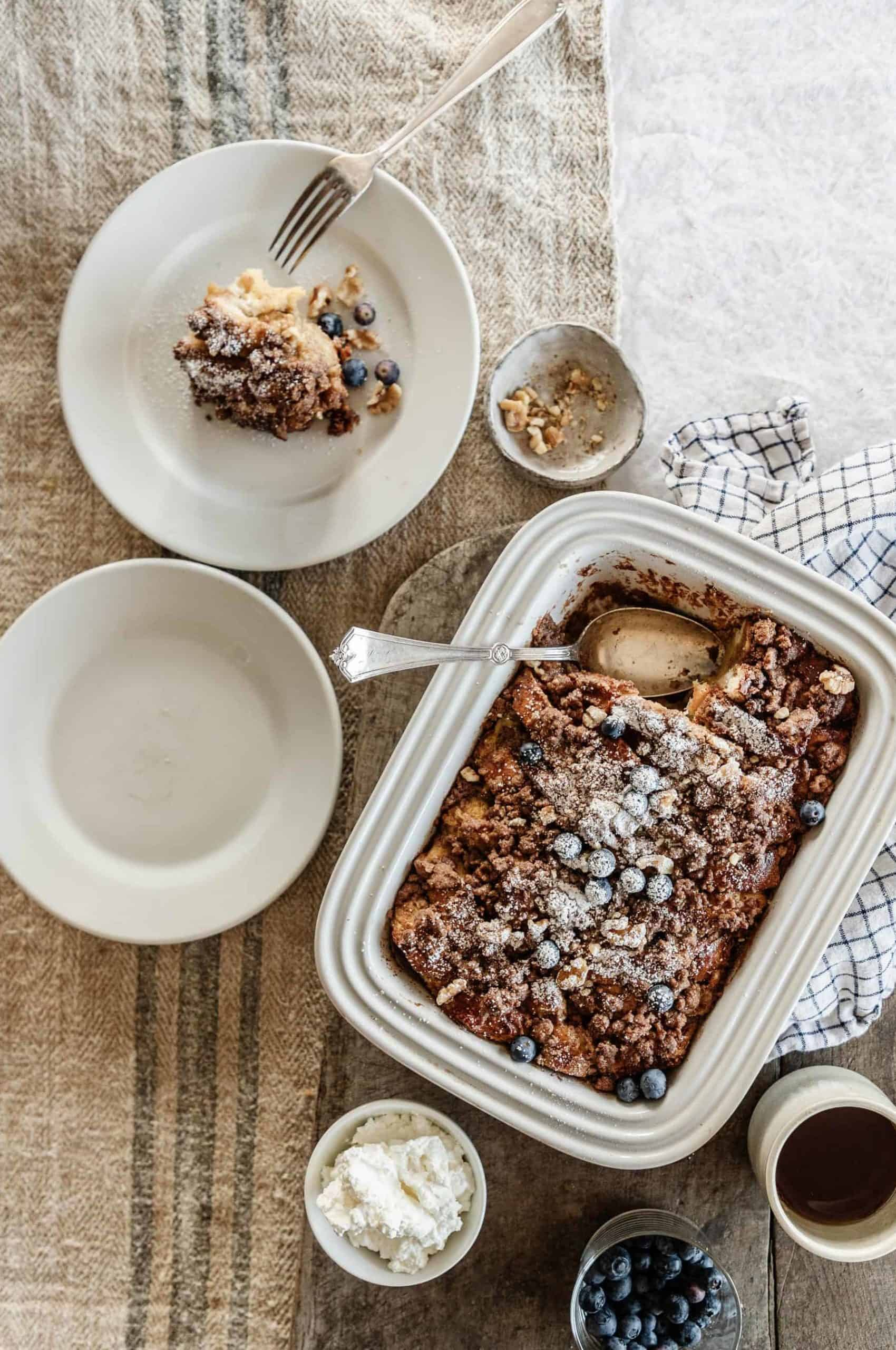 Baked french toast in a white baking dish served with whipped cream, blueberries, maple syrup and topped with powdered sugar.