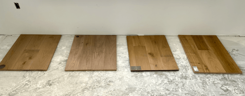 Four samples of engineered hardwood floors laid on a concrete slab for consideration.