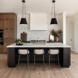 Beautiful kitchen design with black island and oak cabinetry with marble countertops.
