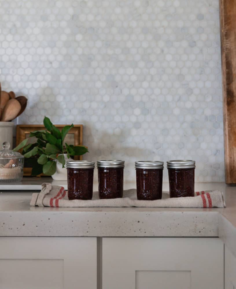 A row of four canned mason jars of fig jam on a kitchen towel.